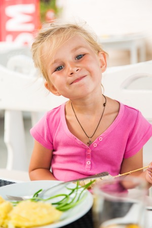 Cute girl eating lunch in outdoor cafe photo