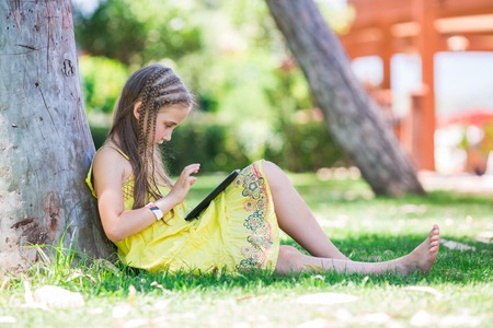cautious: Cute little girl learning with tablet pc in the park Stock Photo
