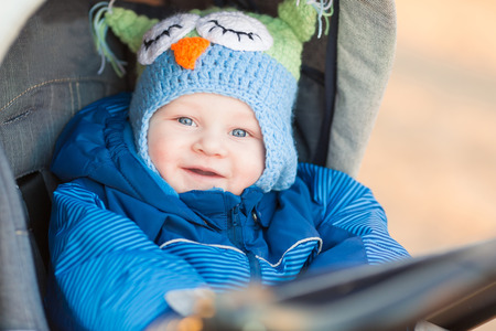 Cute little baby in a stroller outdoor photo