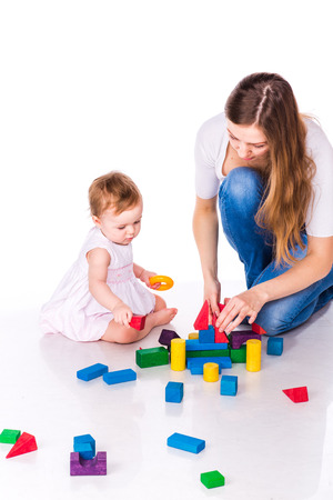 Beautiful baby with mother building a castle with cubes isolated on white Stock Photo