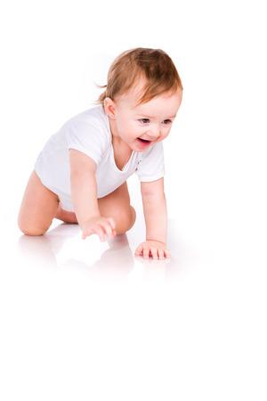 bebe gateando: Pequeño bebé lindo que se arrastra aislado en blanco Foto de archivo