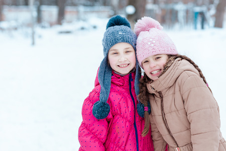 Happy girls playing on snow in winter time photo