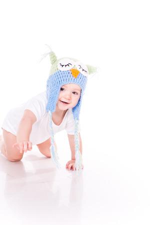 bebe gateando: Peque�o beb� lindo que se arrastra en un sombrero b�ho aislado en blanco