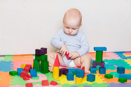 Cute little baby playing with colorful toys at home photo