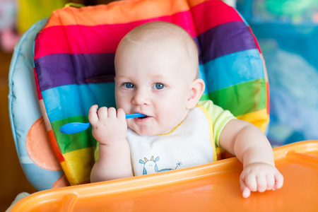 high chair: Adorable baby eating in high chair