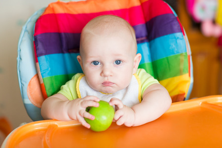 high chair: Adorable baby eating apple in high chair