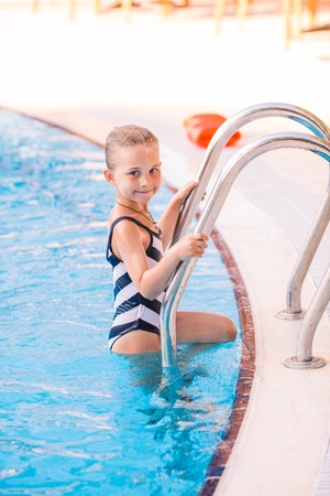 armbands: Cute little girl getting out of swimming pool Stock Photo
