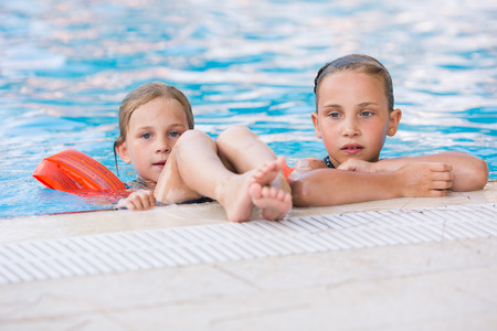 armbands: Two cute little girls in swimming pool posing Stock Photo