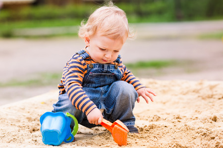 Roztomilý chlapeček hraje s pískem v pískovišti Reklamní fotografie - 40028463