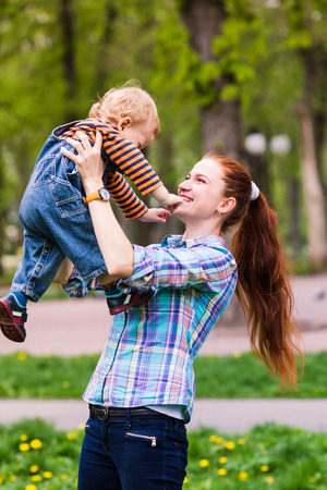 flying kiss: Happy mother with the baby playing outdoor