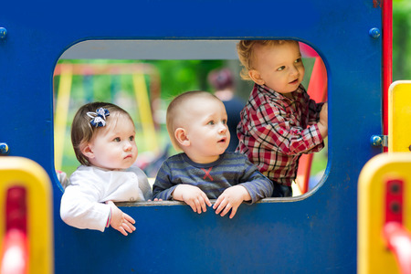 indoor: Three babies in the toy car on the playground