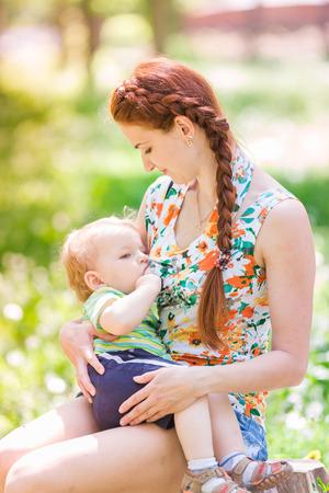 amamantando: Hermosa madre feliz que amamanta a su bebé al aire libre
