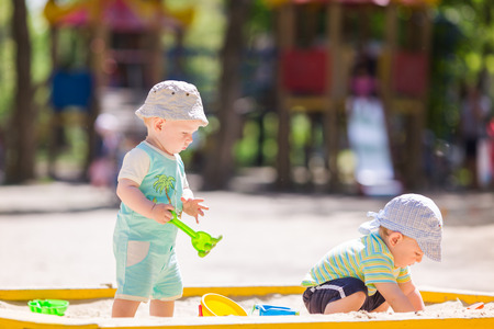sand toys: Two baby boys playing with sand in a sandbox Stock Photo