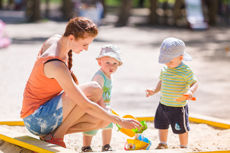 Mother playing helping two baby boys playing with sand in a sandbox