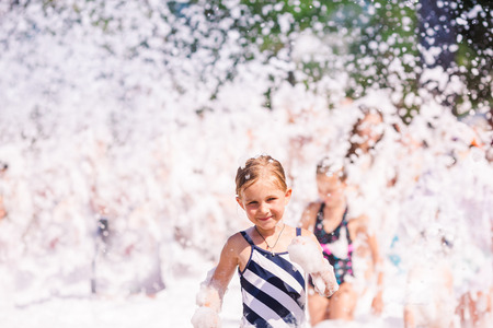 little girl swimsuit: Foam Party on the beach. Cute little girl having fun and dancing.