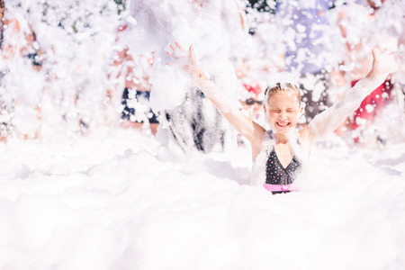 Foam Party on the beach. Cute little girl having fun and dancing. photo