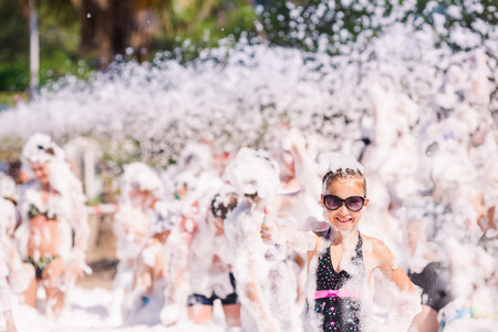 hapiness: Foam Party on the beach. Cute little girl having fun and dancing.