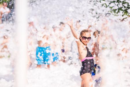 Pěna Party na pláži. Roztomilá holčička baví a tanec. Reklamní fotografie