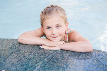 armbands: Cute little girl in swimming pool learning how to swim Stock Photo