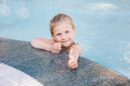 armbands: Cute little girl in swimming pool with thumb up Stock Photo