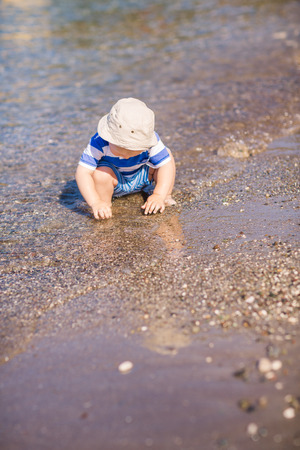 exploring: Cute little baby boy exploring the beach at the seaside