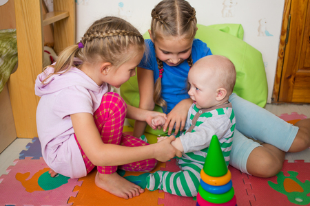 baby playing: Happy kids playing with little brother in the room