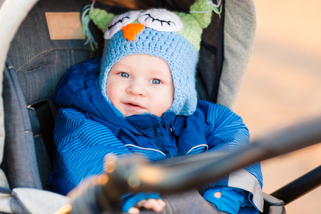 young boy: Cute little baby in a stroller outdoor