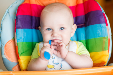 solid food: Adorable baby eating in high chair. Babys first solid food