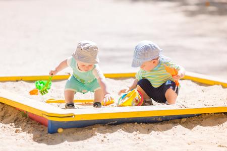 Dwie baby chłopców gry z piasku w piaskownicy