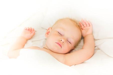 durmiendo: Bebé pacífica acostado en una cama para dormir en sábanas blancas
