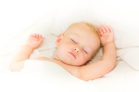 enfant qui dort: Paisible bébé couché sur un lit à dormir sur des draps blancs