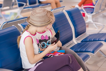 delay: Happy kids waiting for flight inside international airport, playing with tablet PC. Flight delay concept Stock Photo