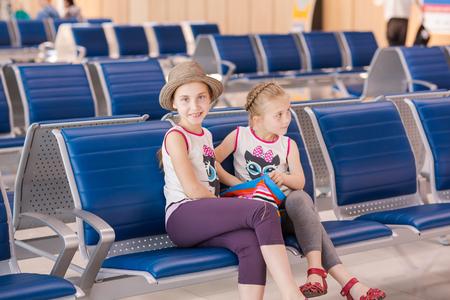 delay: Happy kids waiting for flight inside international airport. Flight delay