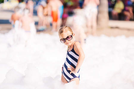 foam party: Foam Party on the beach. Cute little girl having fun and dancing.