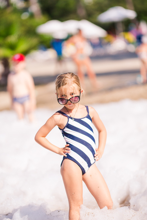 children swimsuit: Foam Party on the beach. Cute little girl having fun and dancing.
