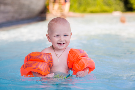 armbands: Cute little baby learning how to swim in swimming pool