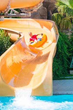 amusment: Cute happy girl in amusment aquapark sliding. Summertime, vacation concept.