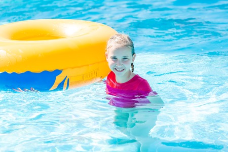Cute happy girl in amusment aquapark sliding. Summertime, vacation concept.