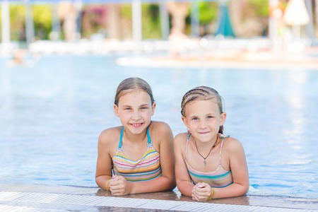 amusment: Cute happy girls at the pool in amusment aquapark. Summertime, vacation concept. Stock Photo