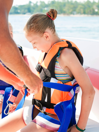 Happy little girl wearing safety jacket, preparing for parasailing ride, extreme sport