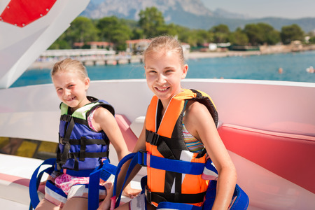 Two happy little girls wearing safety jackets preparing for parasailing ride, extreme sport