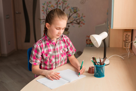 Cute little girl writing her homework at the table