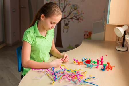 Cute little girl creating toys with chenille sticks at the table. Creativity and handmade concept.