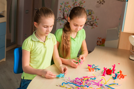 Cute little girls creating toys with chenille sticks at the table. Creativity and handmade concept.