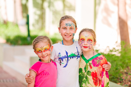 Happy little girls with face art paint in the park. Childs birthday masquerade party, friends having fun, laugh and hugging each other. Entertainment and holidays.
