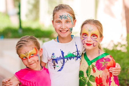 Happy little girls with face art paint in the park. Child's birthday masquerade party, friends having fun, laugh and hugging each other. Entertainment and holidays.