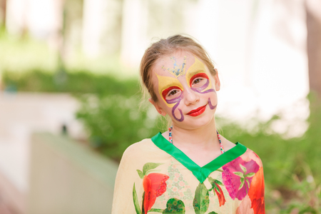 Happy little girl with face art paint in the park. Childs birthday masquerade party have fun, laugh. Entertainment and holidays.