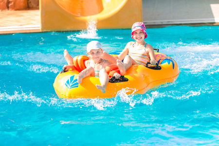 Cute happy girls in amusment aquapark. Summertime, vacation concept.