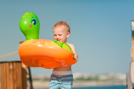 Cute little boy playing with life buoy at the seaside. Summertime, vacation concept. Reklamní fotografie