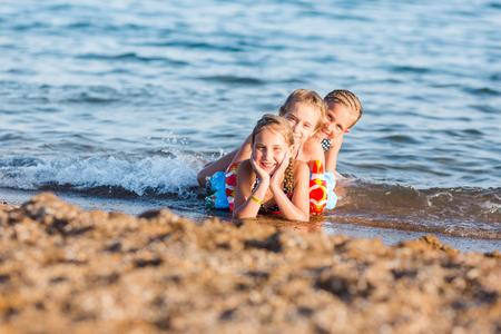 Happy kids on the beach having fun. Summer holiday concept Reklamní fotografie